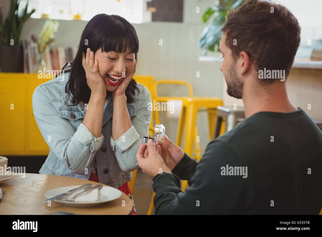 Young man gifting ring to shocked happy woman in cafe - Stock Image