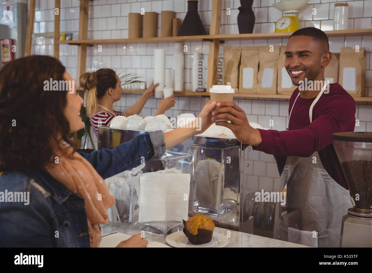 Smiling owner serving coffee to woman at cafe - Stock Image
