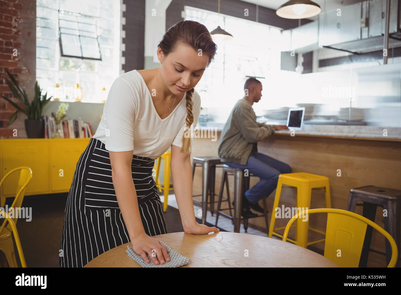 Young waitress cleaning table at cafe - Stock Image