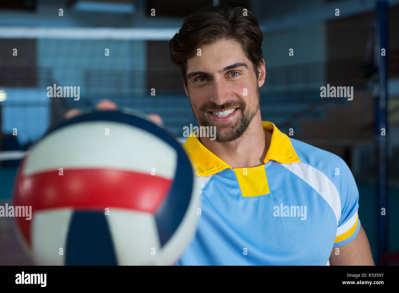 Portrait of male sportsperson with volleyball at court - Stock Image