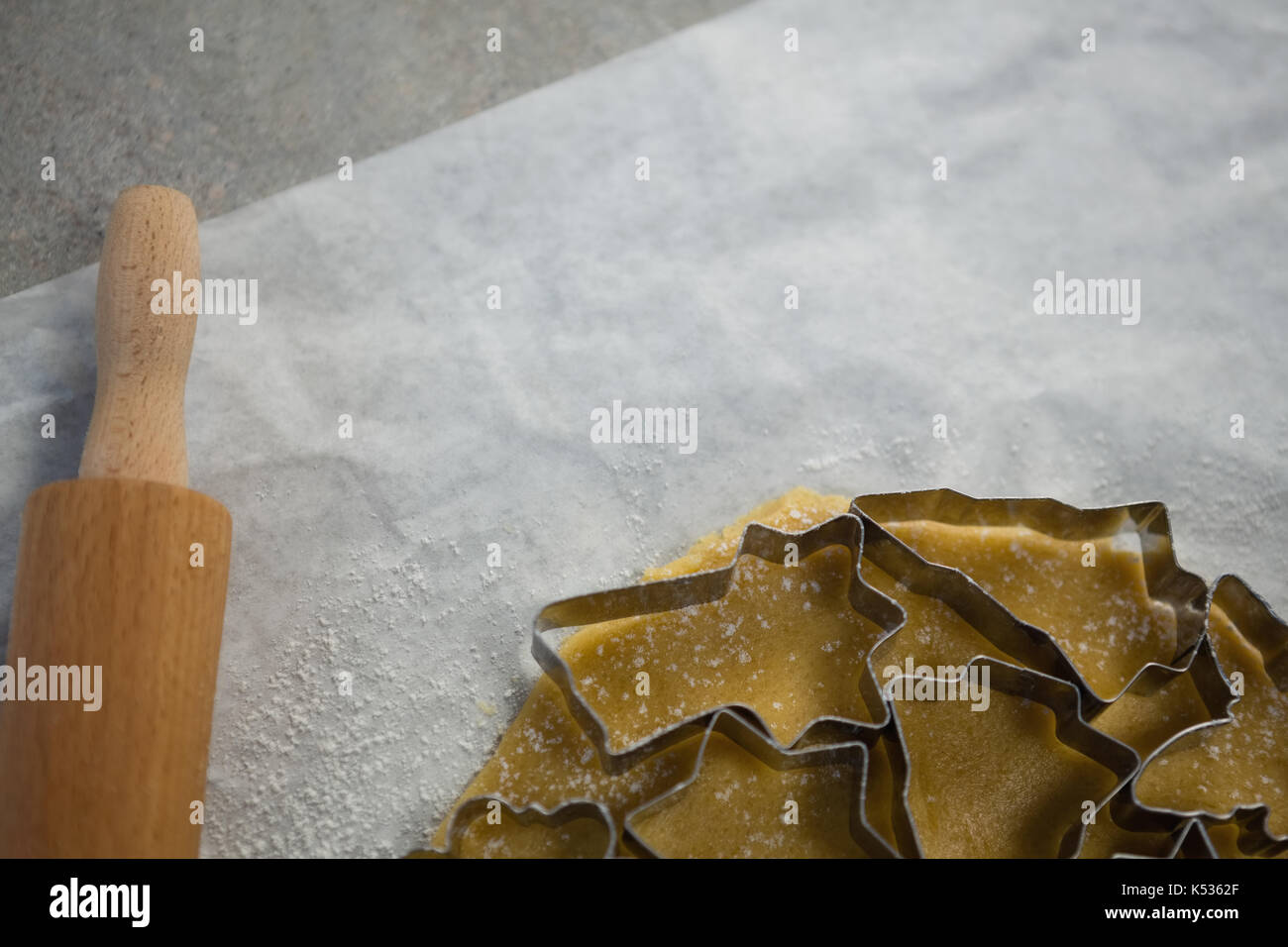 Cropped image of various pastry cutters over dough on wax paper at table - Stock Image