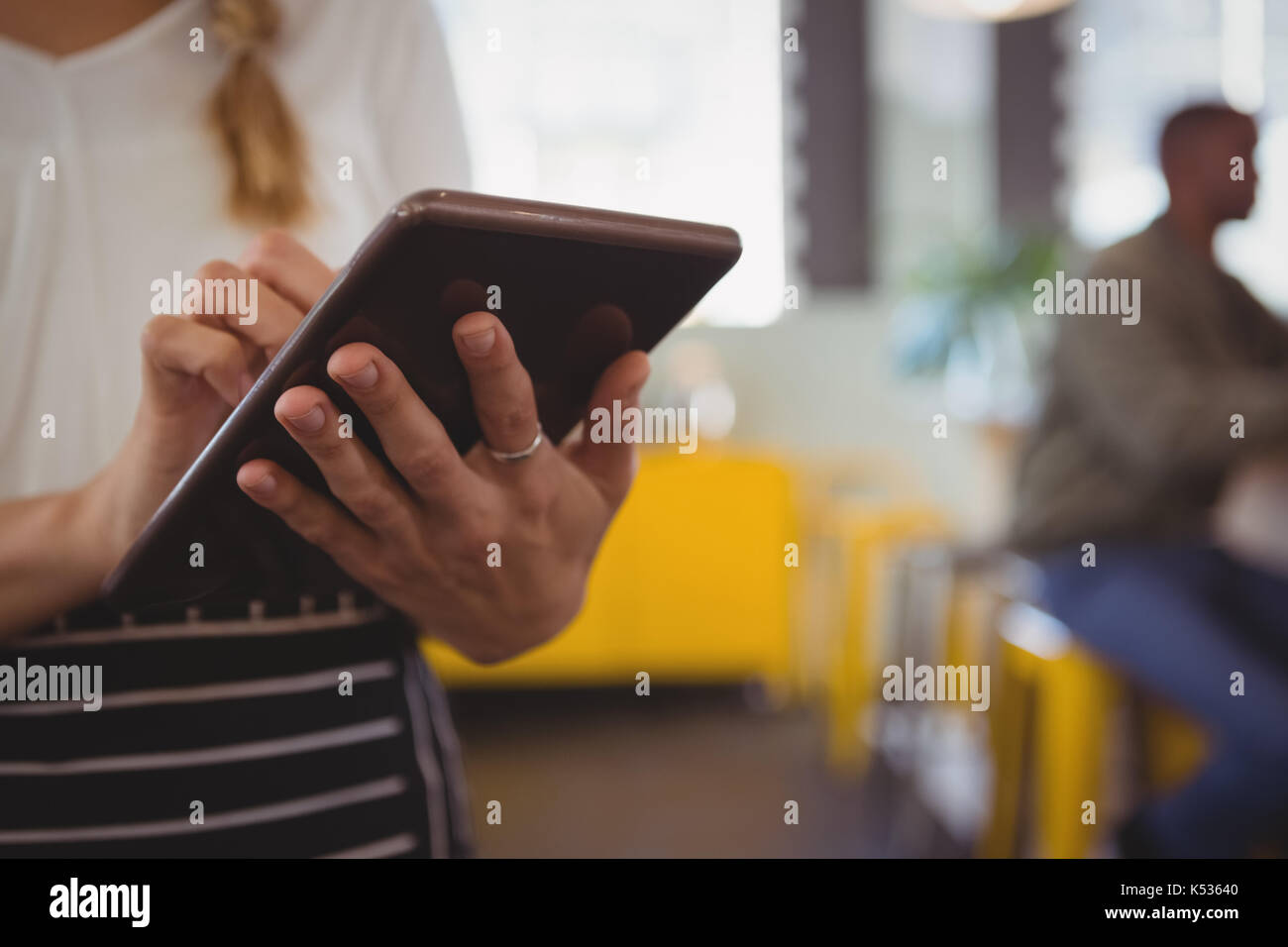 Mid section of waitress using digital tablet at cafe - Stock Image