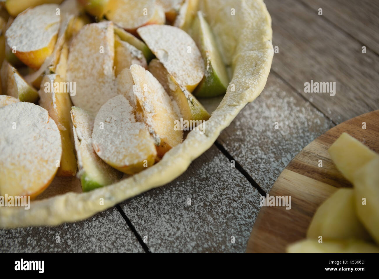 High angle view of powdered sugar on apple slices in baking pan on table - Stock Image