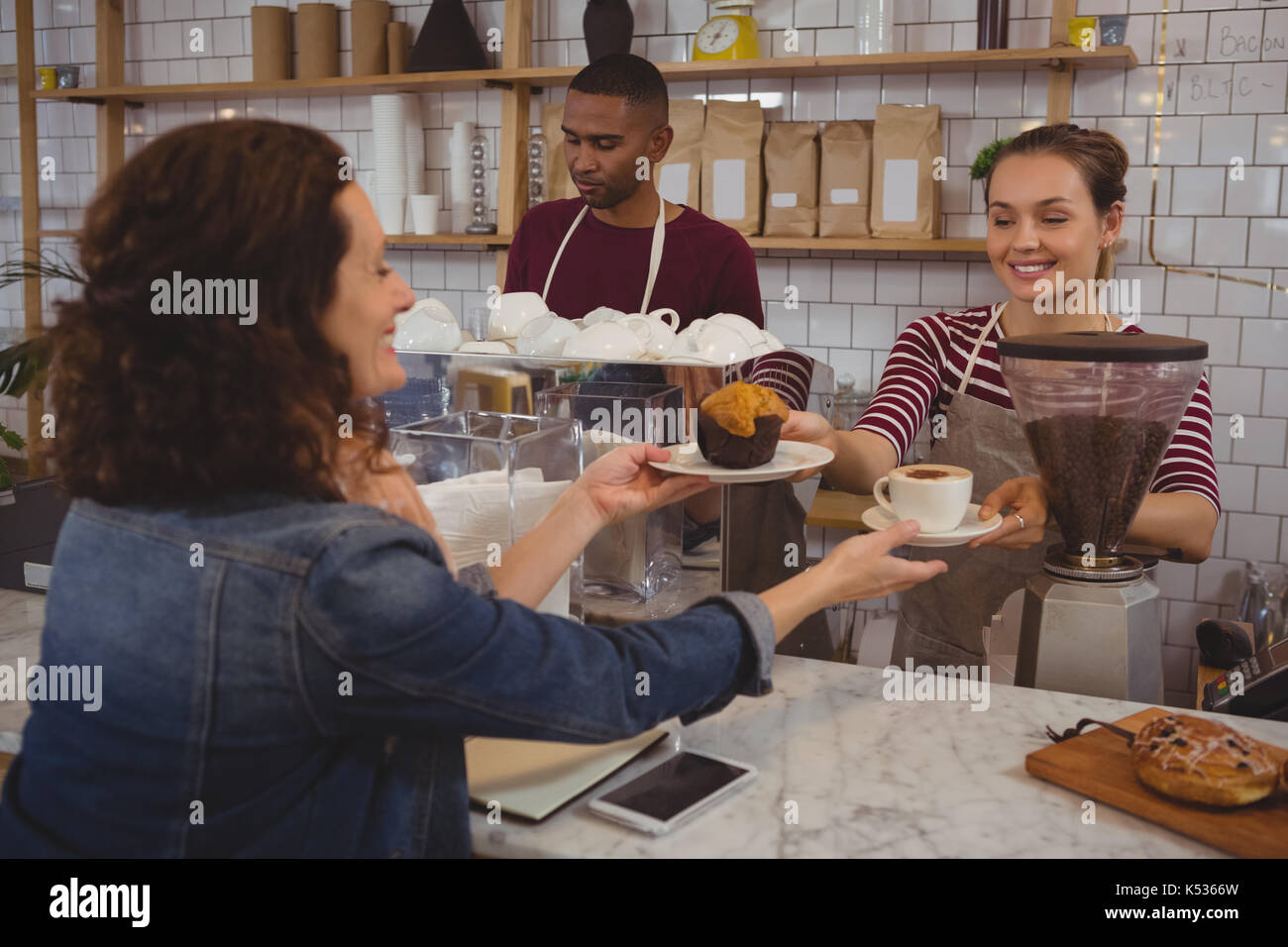 Female owner serving muffin and coffee to customer at cafe - Stock Image