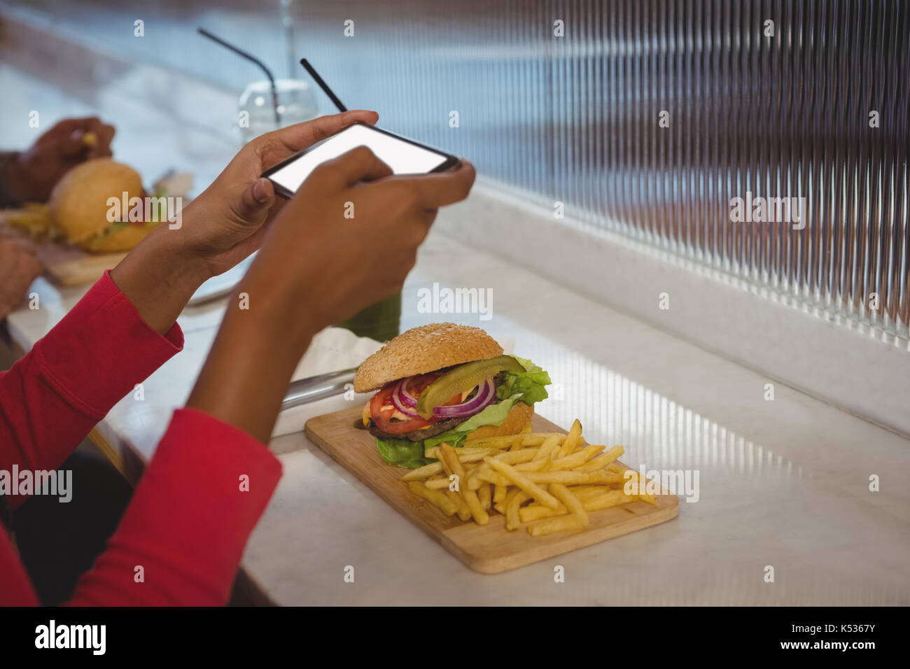 Cropped hands of woman photographing French fries and burger at counter in cafe - Stock Image
