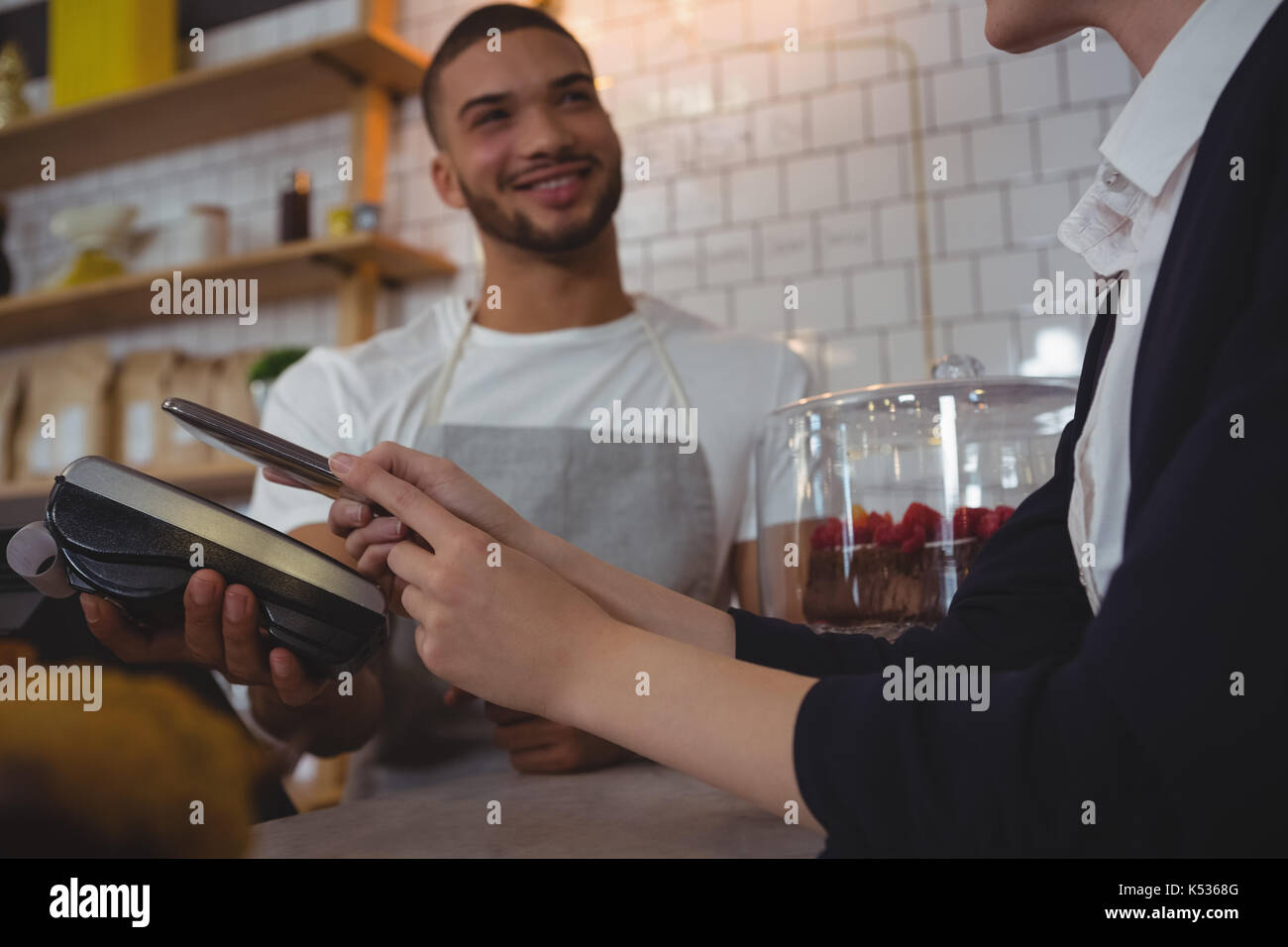 Waiter showing credit card reader to female owner at counter in cafe - Stock Image
