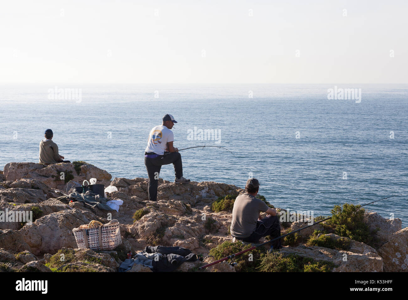 Sagres, Portugal: Local men fishing at Cape St. Vincent from Sagres Point. The cape is the southwestern most point Stock Photo
