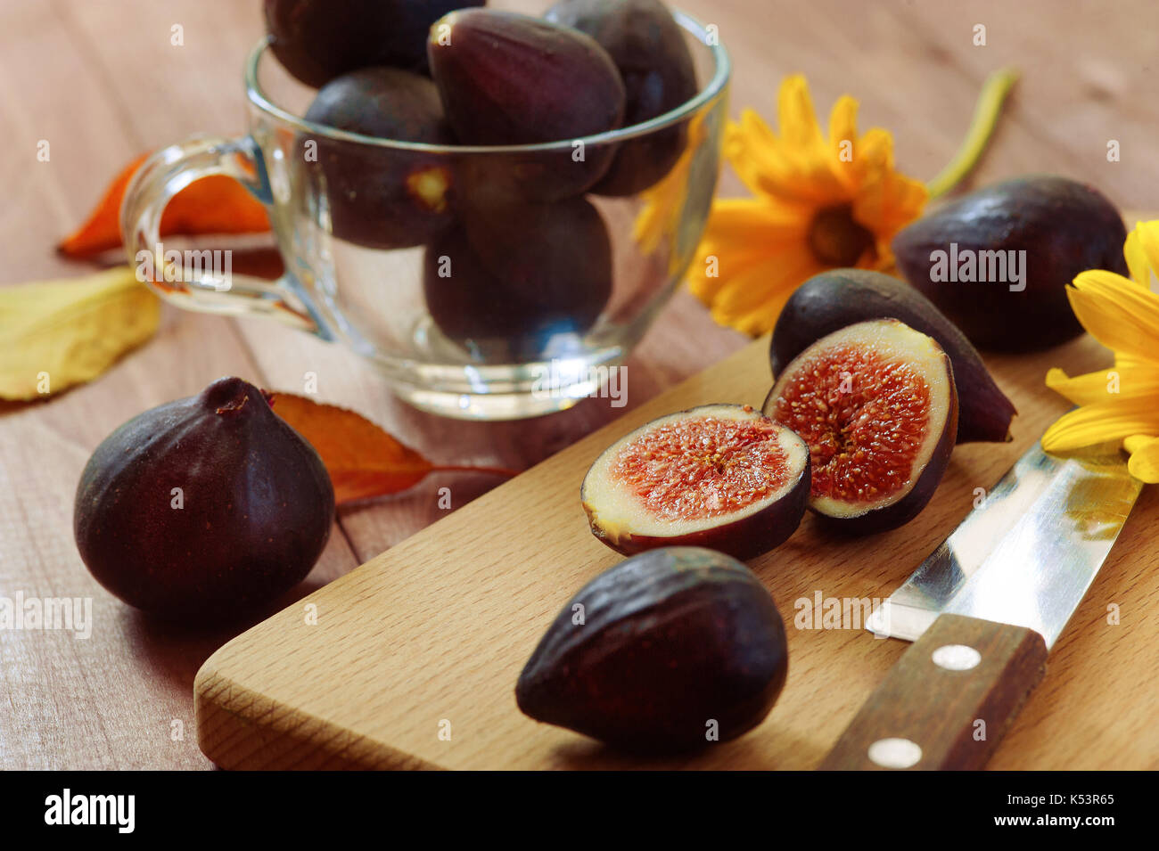 Bright autumn composition of figs, dry flowers and tree branches on wood background. Flat lay, top view - Stock Image