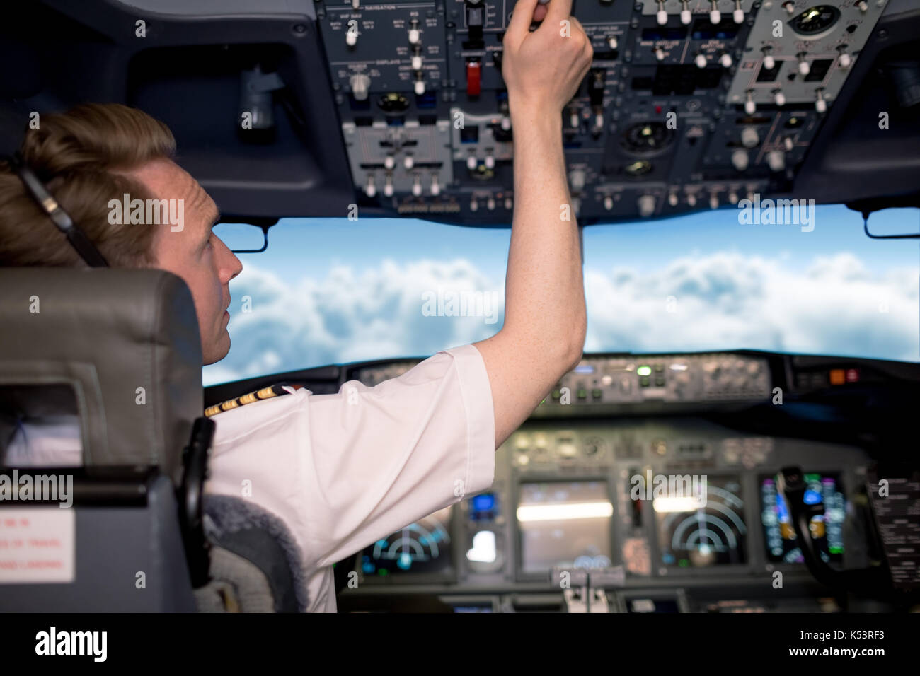 Young male pilot switching controls in airplane cockpit - Stock Image