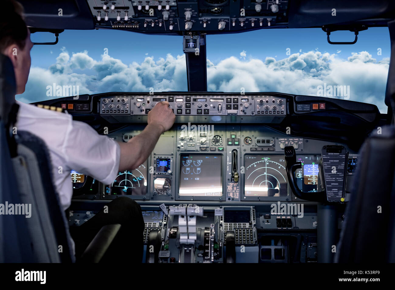 Rear view of young male pilot switching controls in airplane cockpit - Stock Image