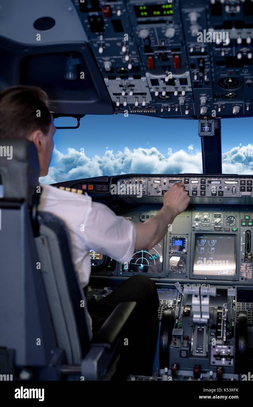 Young male pilot switching controls in air vehicle cockpit - Stock Image