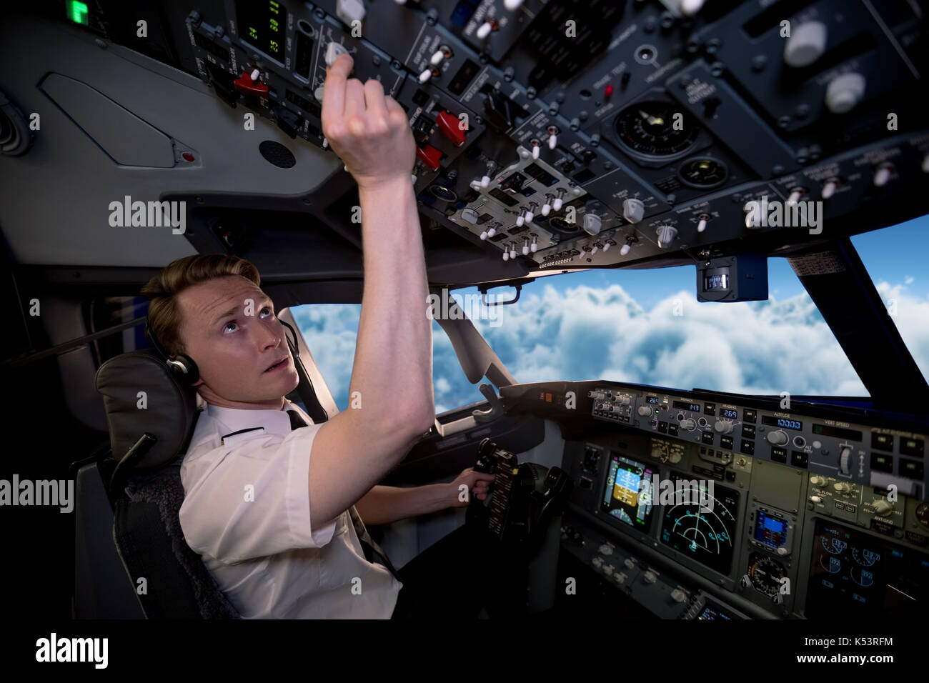 Side view of young male pilot switching controls in airplane cockpit - Stock Image