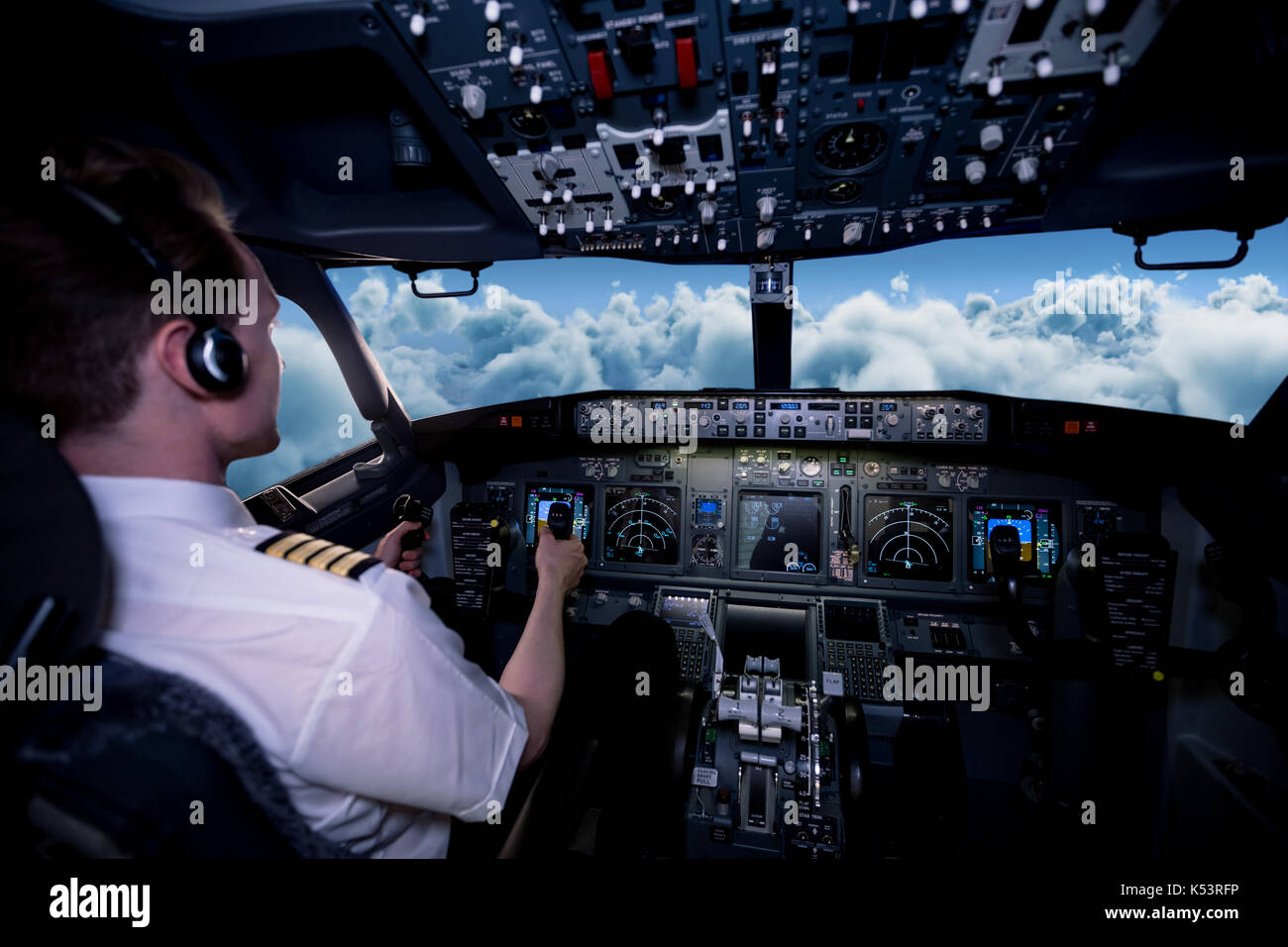 Young male pilot flying airplane from cockpit - Stock Image