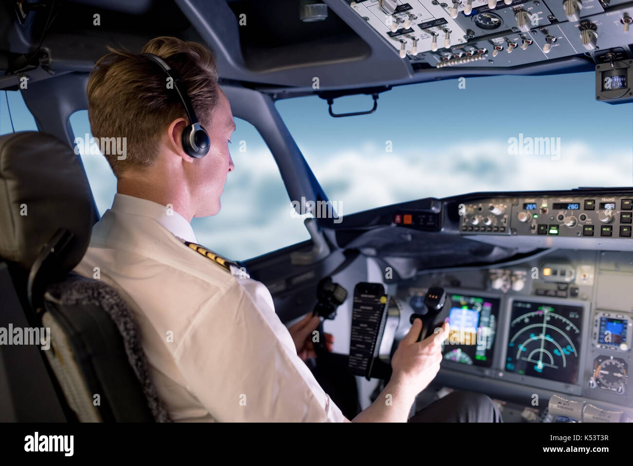 Young male pilot flying airplane while sitting in cockpit - Stock Image