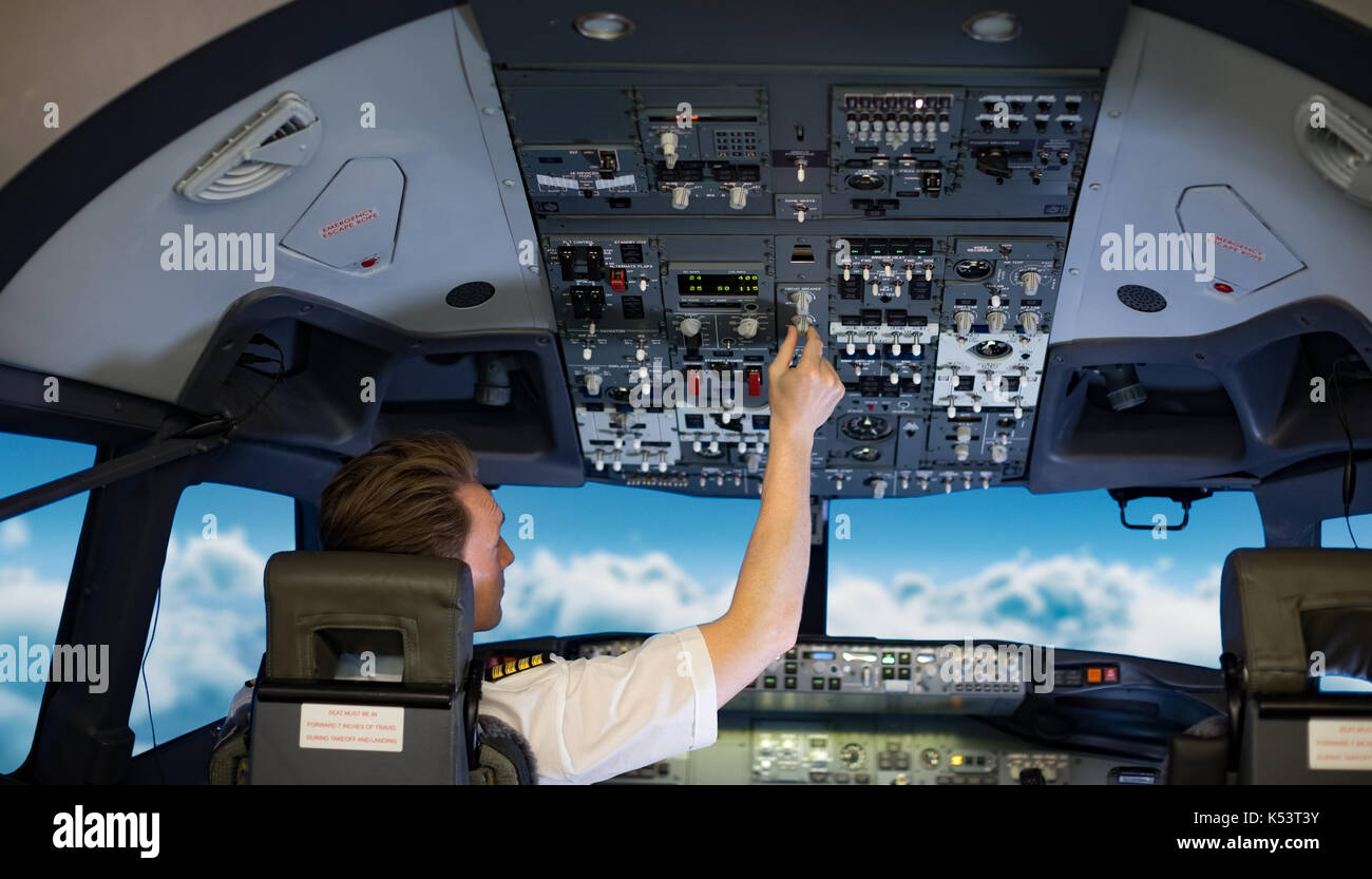 Rear view of young male pilot switching controls in air vehicle cockpit - Stock Image