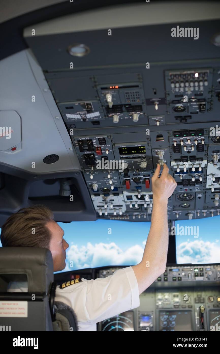 Rear view of male pilot switching controls in air vehicle cockpit - Stock Image
