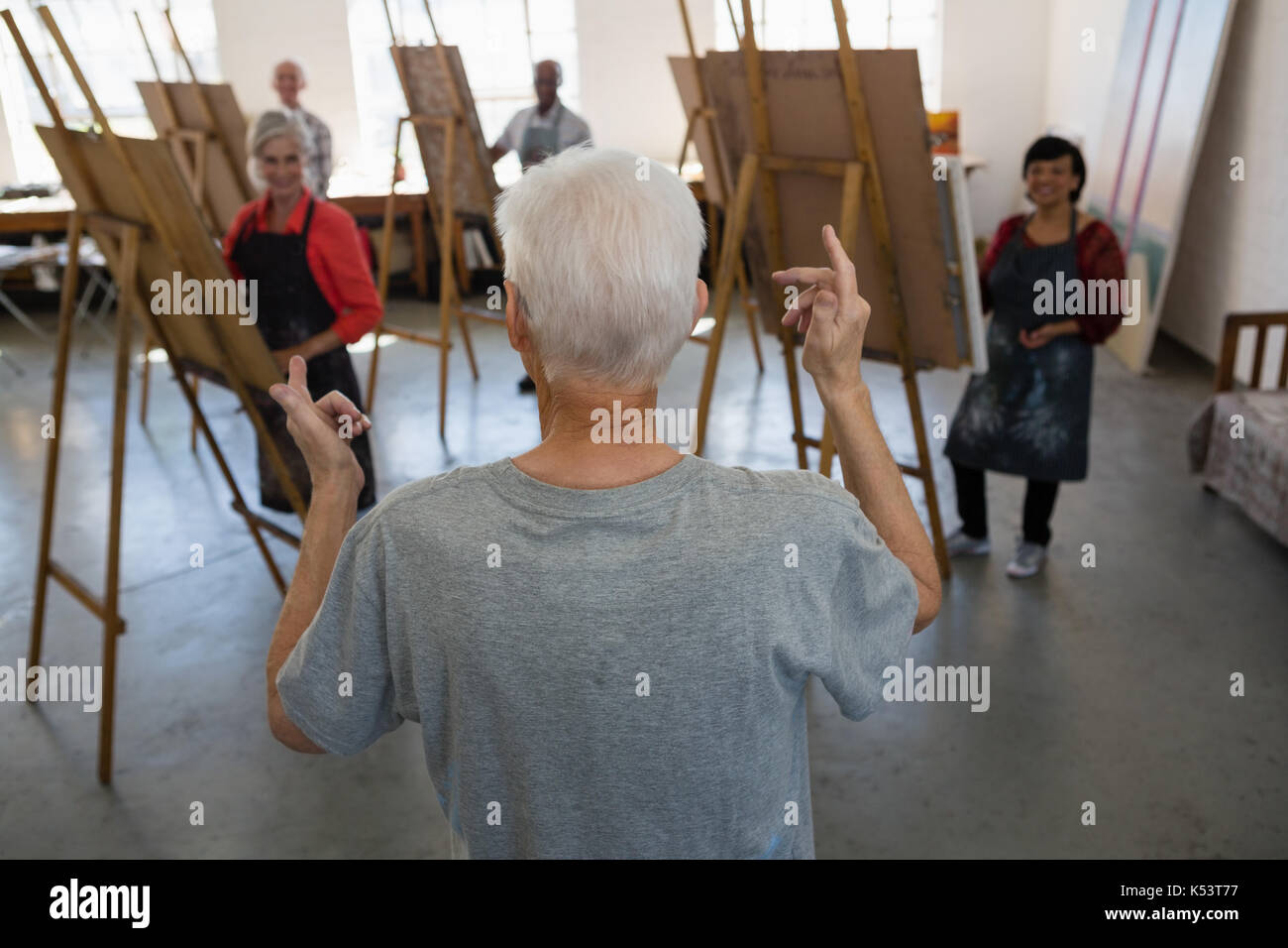High angel view of man gesturing while standing against friends in art class - Stock Image