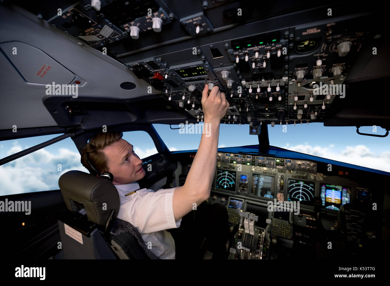 Handsome young pilot switching controls in airplane cockpit - Stock Image