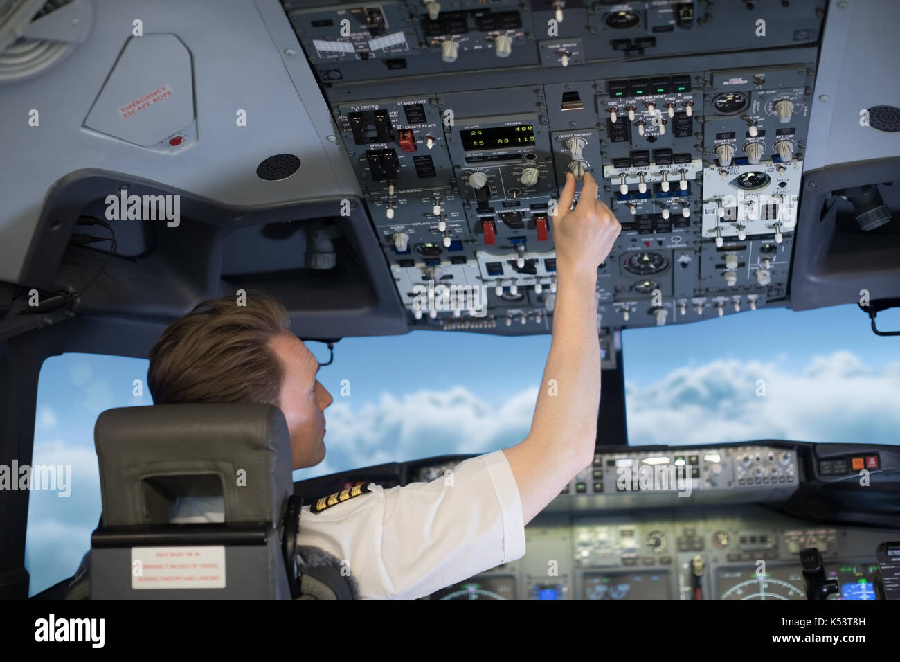 Rear view of pilot switching controls in airplane cockpit - Stock Image