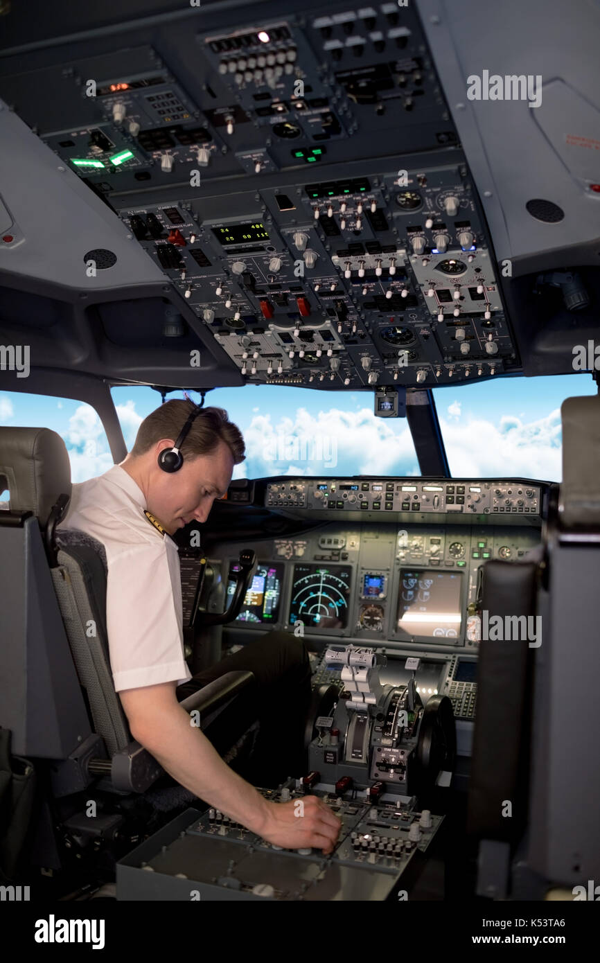 Rear view of male pilot switching controls in airplane cockpit - Stock Image