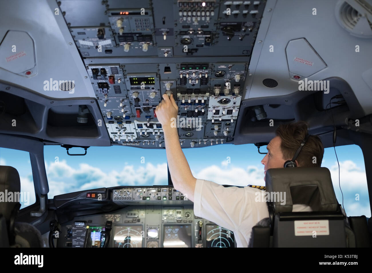 Rear view of male pilot switching controls on dashboard in airplane cockpit - Stock Image