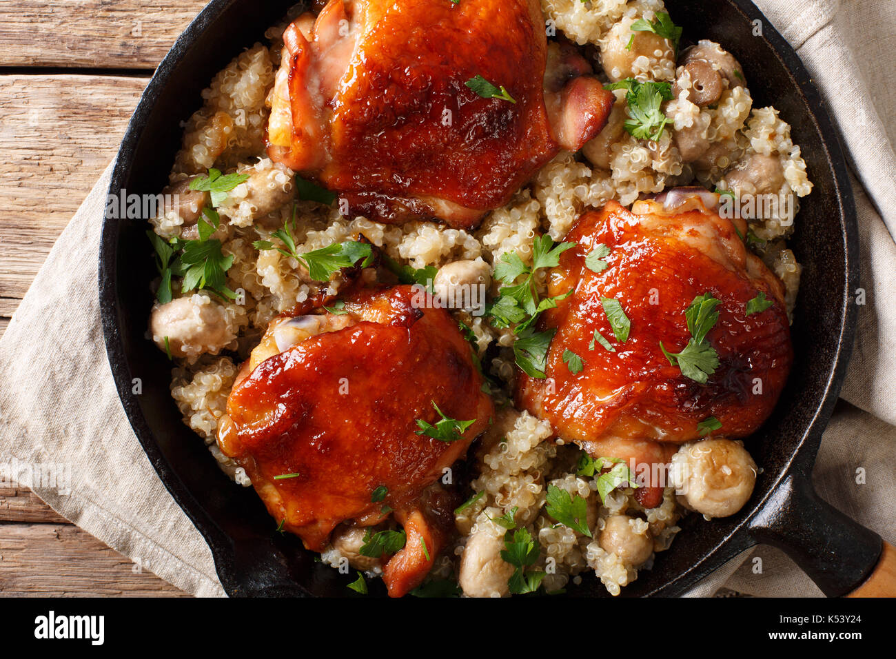 One pot: fried chicken thighs with quinoa and mushrooms close-up on the table. top view from above horizontal Stock Photo