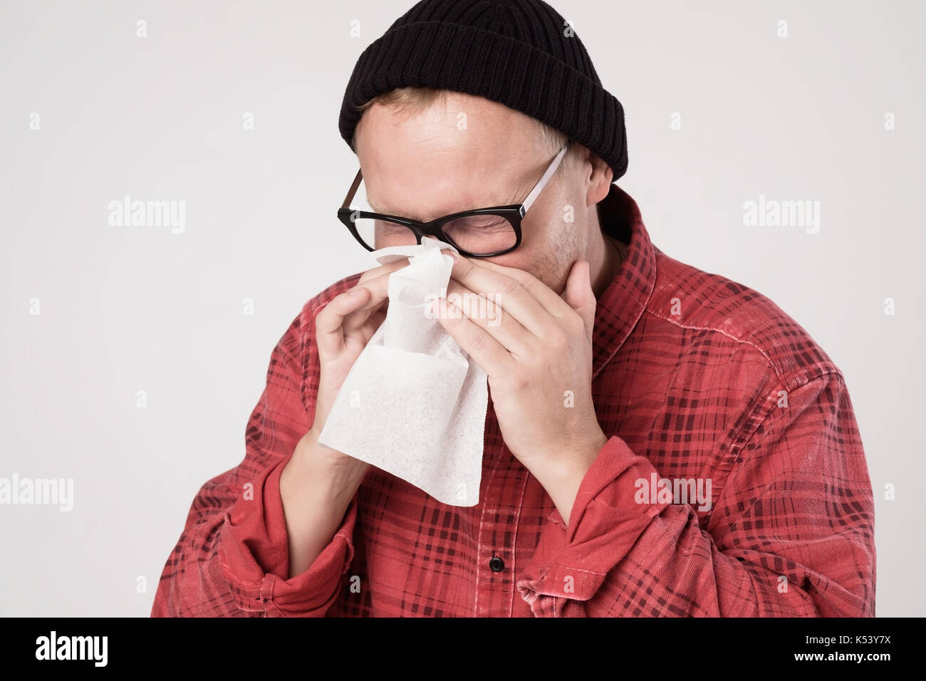 Caucasian Man with handkerchief sneezing feeling unwell - Stock Image