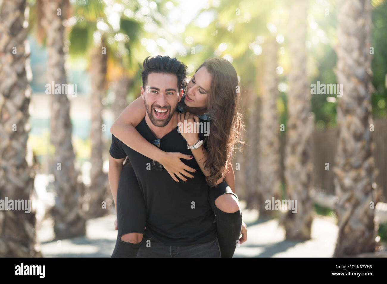 Portrait of young happy man giving his girlfriend a piggyback ride - Stock Image