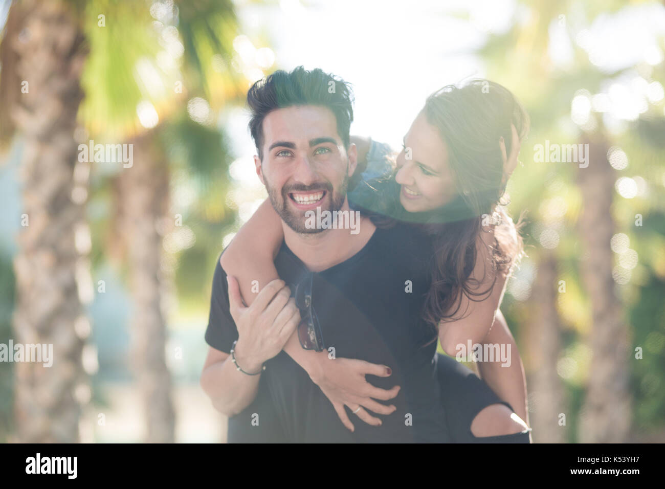 Portrait of happy young man giving his girlfriend a piggy back ride - Stock Image