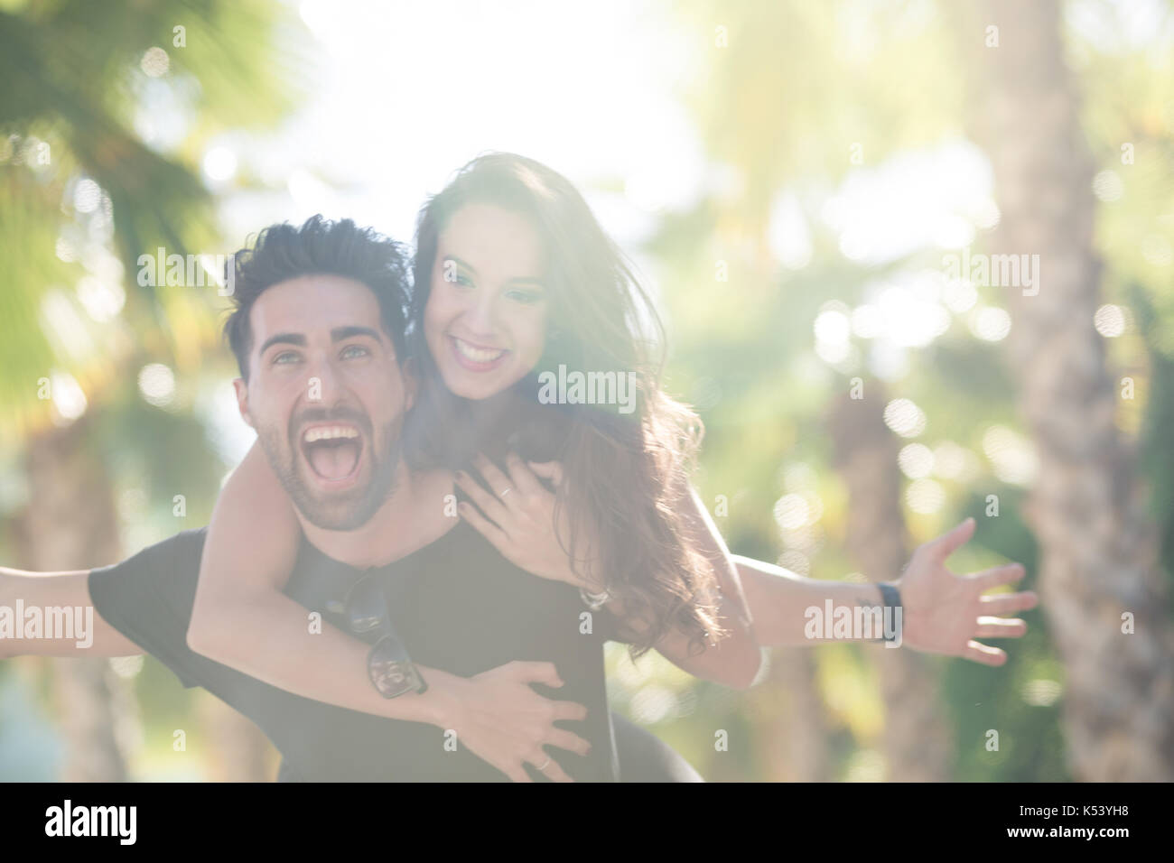 Portrait of happy man with spread arms giving his girlfriend a piggy back ride - Stock Image