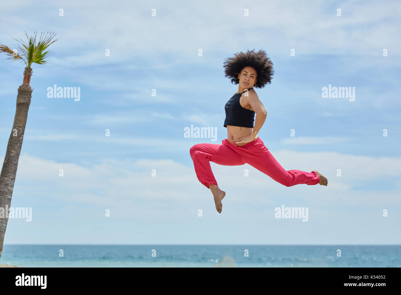 Portrait of young sportswoman jumping on beach with hands on waist Stock Photo