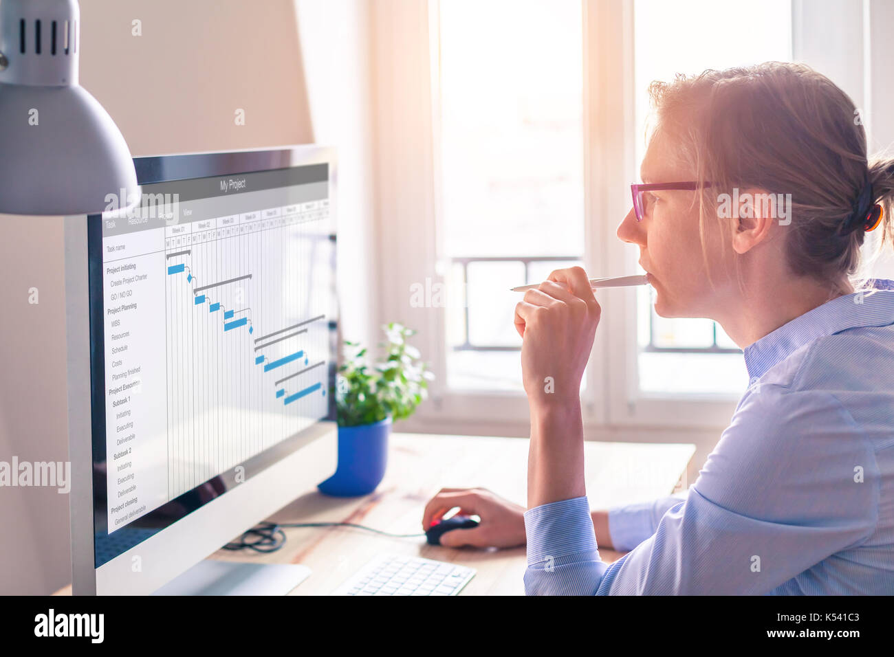 Female project manager using Gantt chart schedule to organize tasks and update planning on computer screen with software - Stock Image