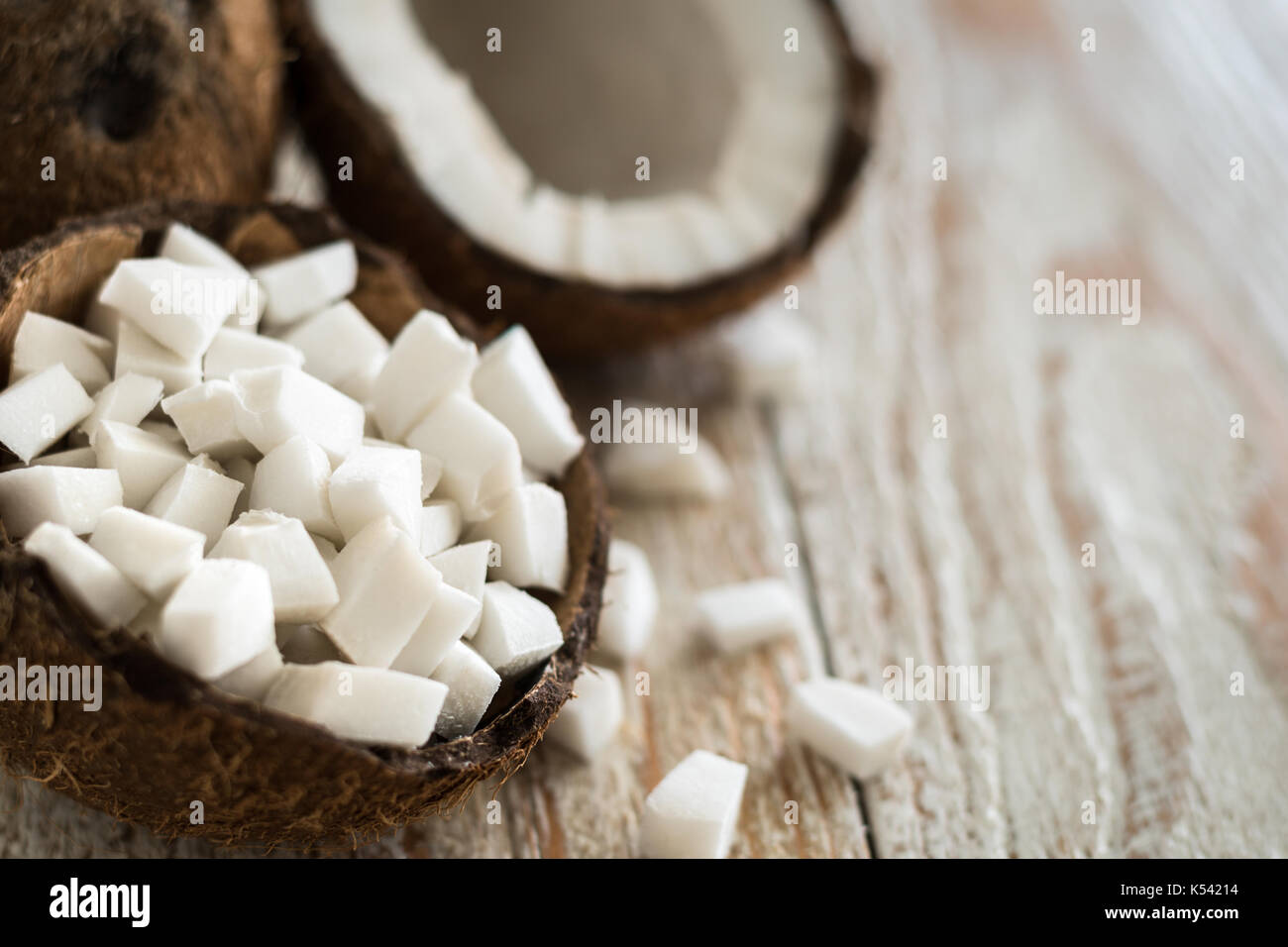 Coconut pieces in shell with coconut on background - Stock Image