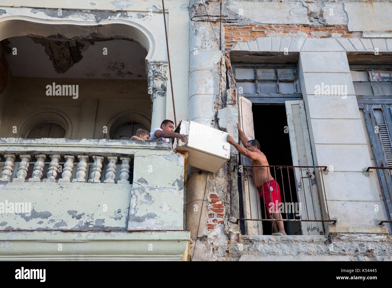 Havana locals move a fridge from one balcony to another in Havana in Cuba in the Caribbean - Stock Image