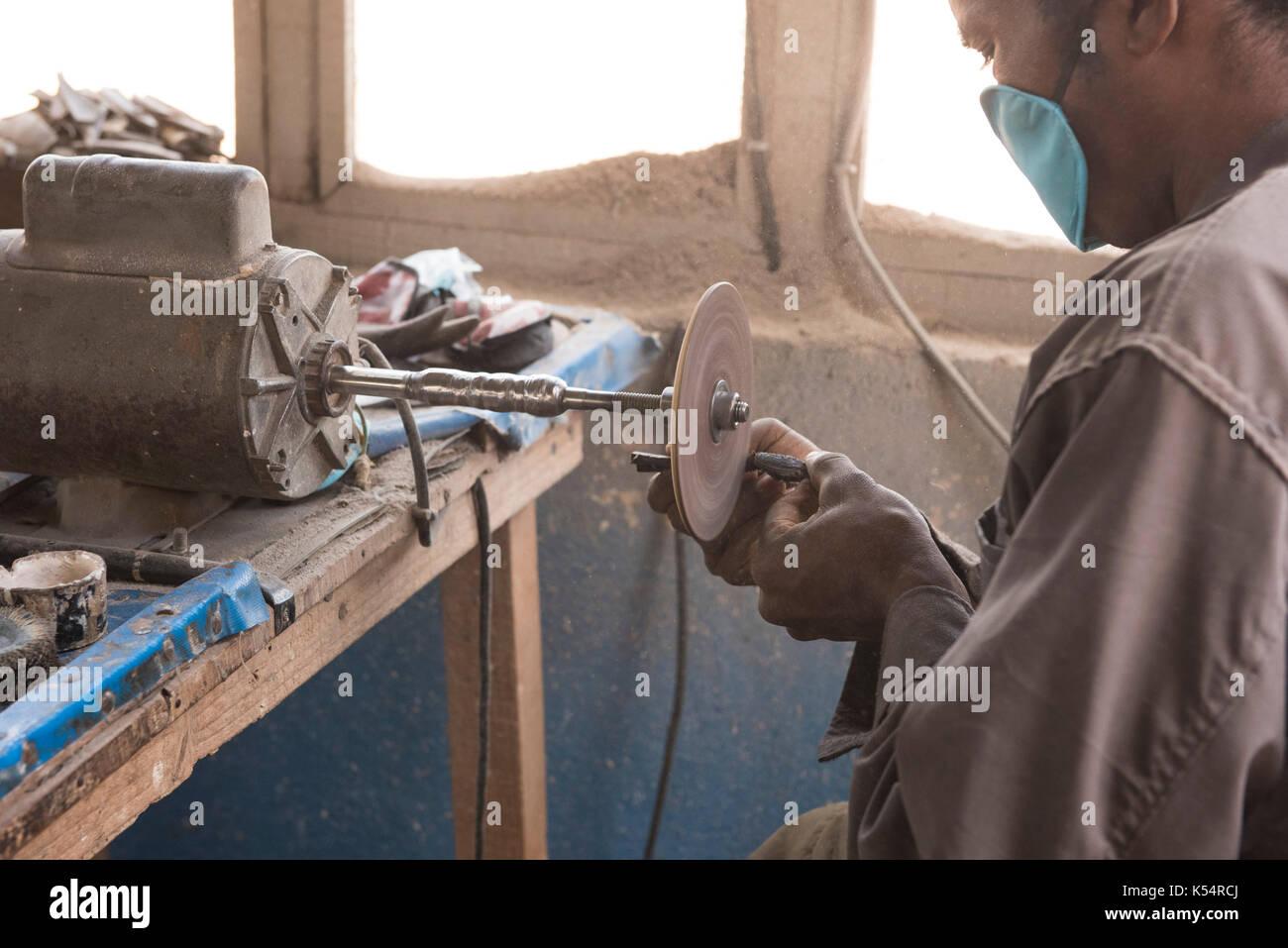 Artisan at work in zebu horn craft workshop, Maminirina cornet des zebu, Antsirabe, Madagascar - Stock Image
