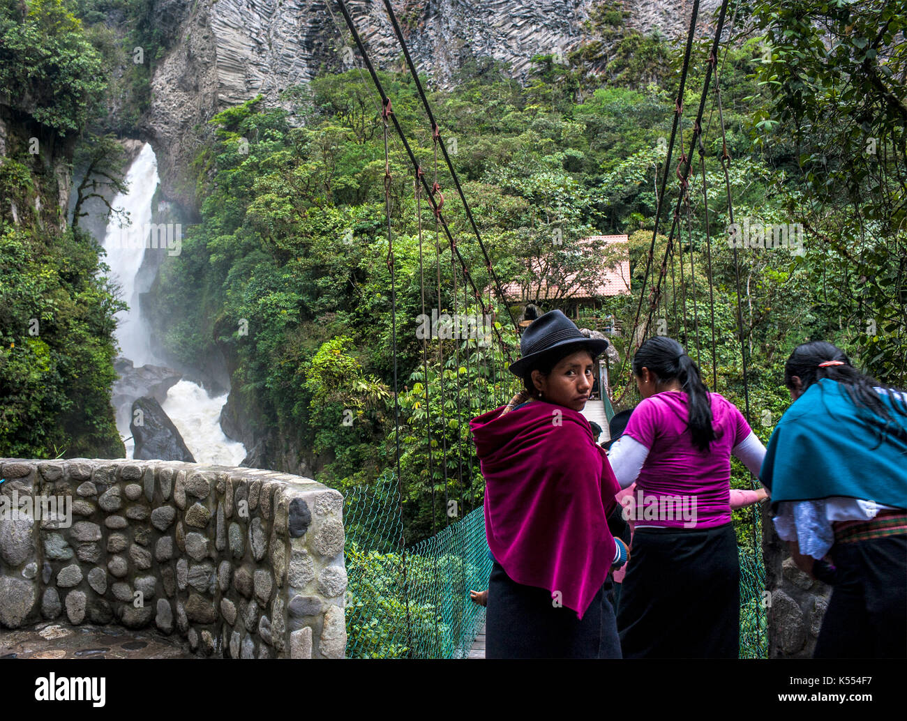 Banos de Agua Santa, Cascades route, Ecuador - May 1, 2012: Indigenous women walk across the bridge under Devil's Cauldron waterfall (spanish: Pailon  - Stock Image
