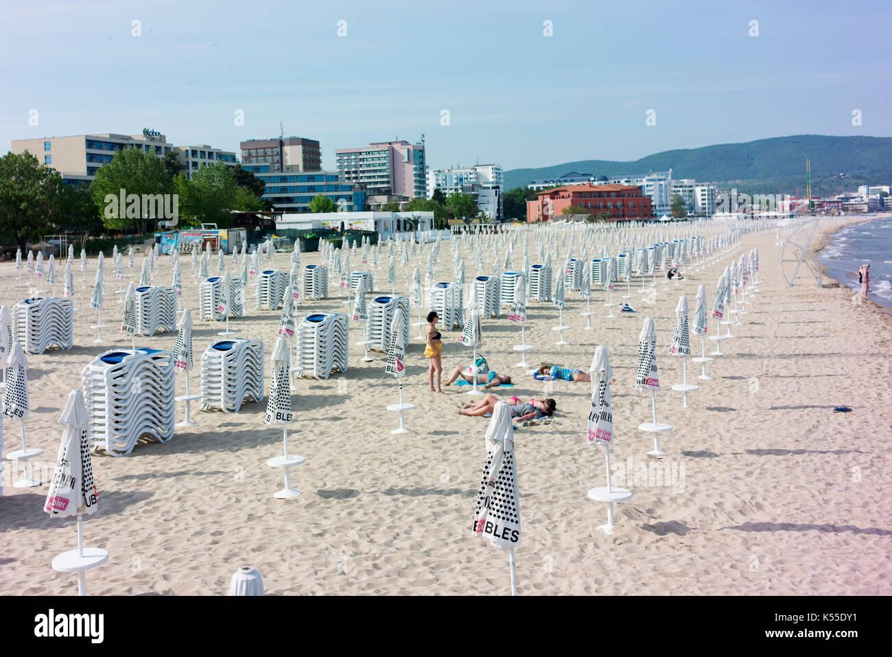 People sunbathe on a near-empty beach at Sunny Beach well before high season. - Stock Image