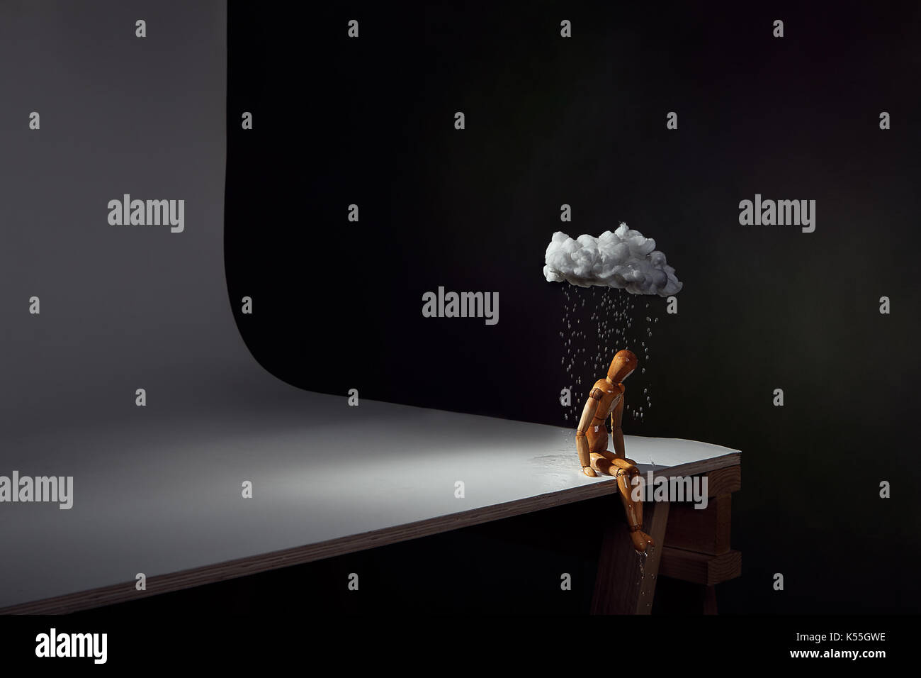 Personal Rain Cloud.  A lonely man sits under a small rain cloud, feeling sad, left out, ignored.  Having a bad day.  Conceptual studio shot. - Stock Image