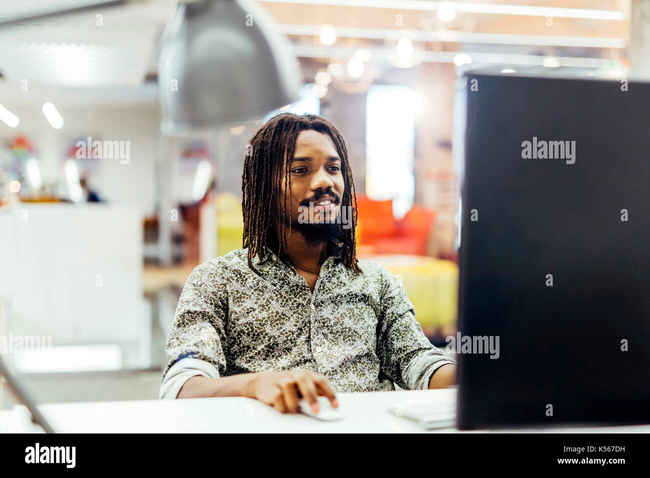 Handsome designer working on a computer - Stock Image