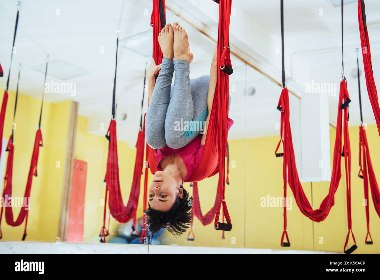 Young women doing yoga exercise or aerial yoga antigravity in the studio. Stock Photo