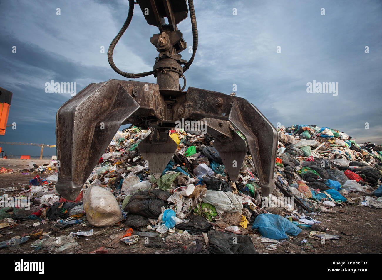 Close up of mechanical arm grabbing waste from a pile at city landfill - Stock Image