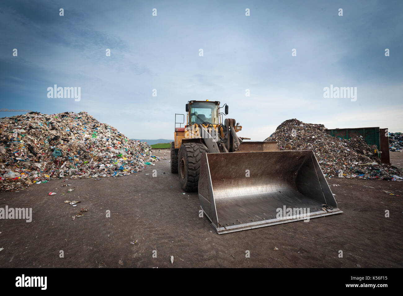 Bulldozer in front of pile of waste at city landfill. - Stock Image