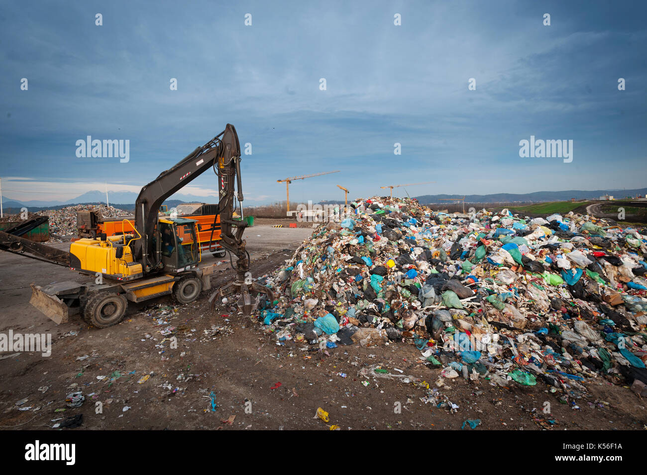 Bulldozer with mechanical arm grabbing waste from a pile at city landfill. Waste management, ecology concept. - Stock Image