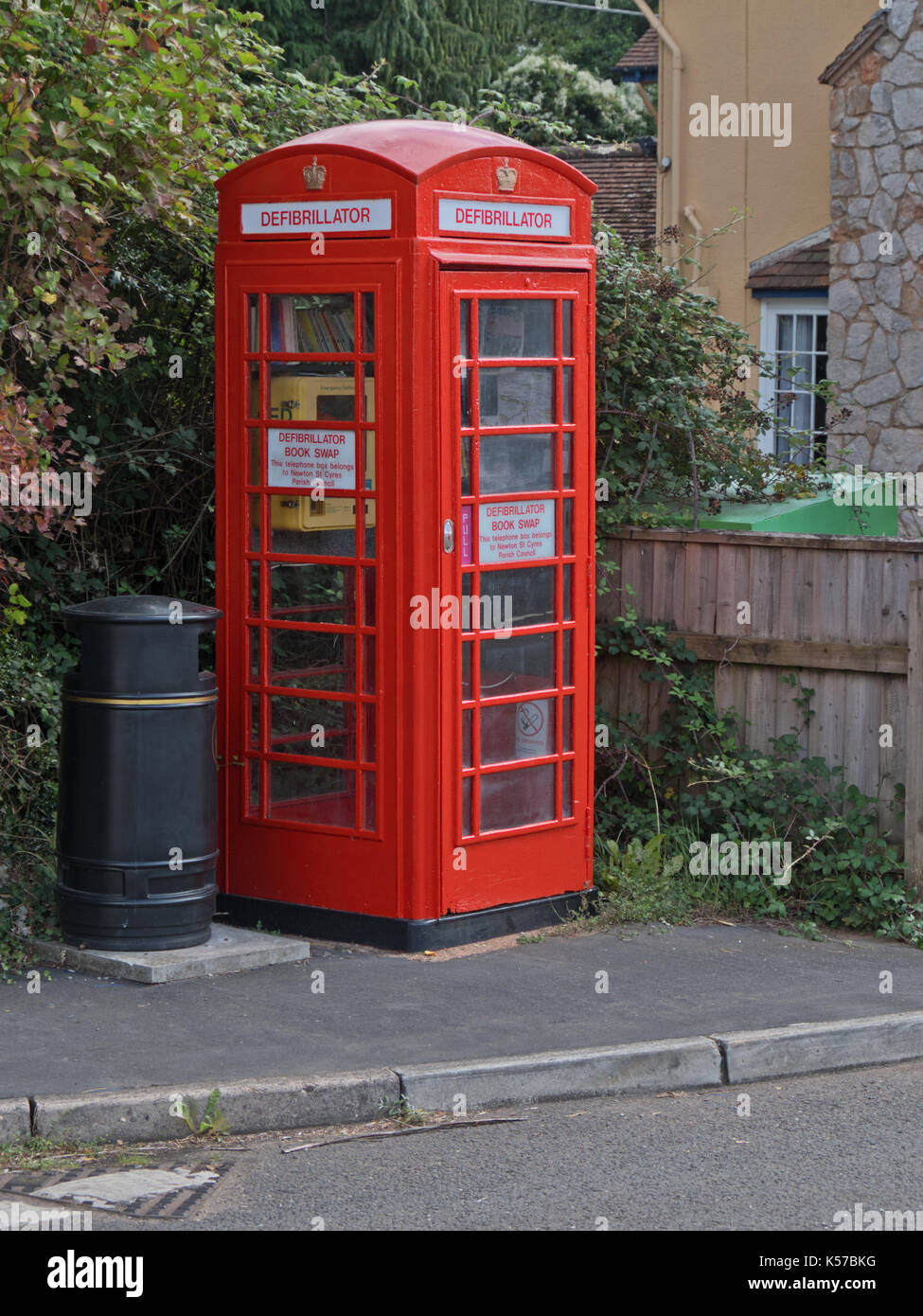 A disused public telephone box put to dual use housing an automated defibrillator for treating cases of cardiac arrest, as well books for exchange - Stock Image