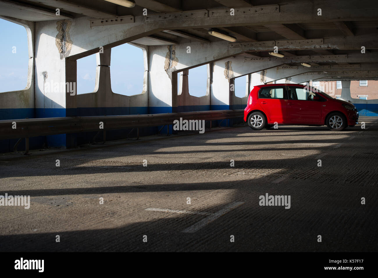 A small red car parked in a empty multistorey car park. - Stock Image