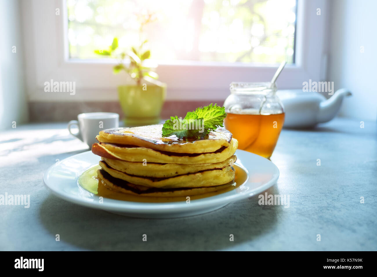 Pancakes heap with sprig of mint and maple syrup - Stock Image