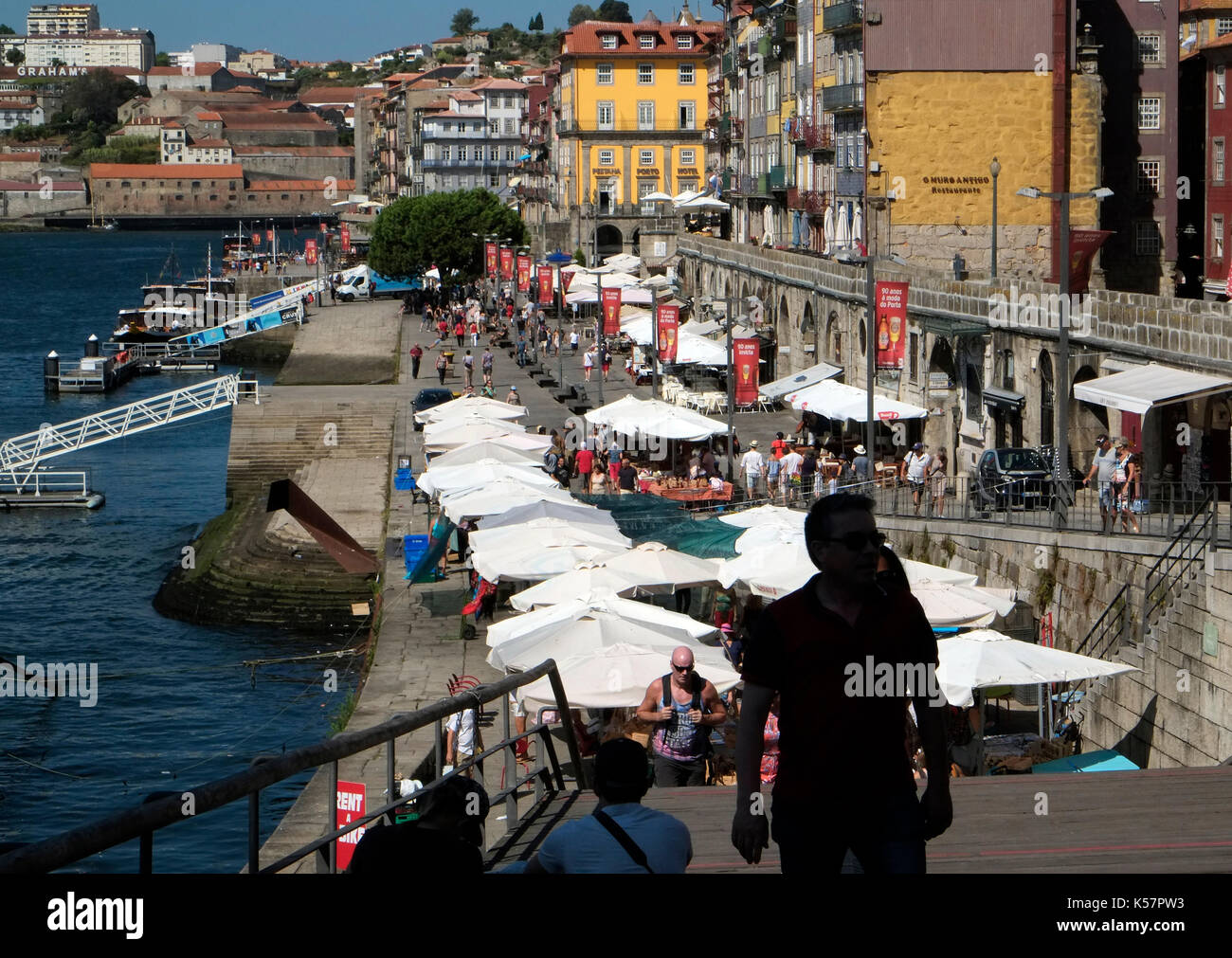 Tourists walk past al fresco restaurants by the riverside area in the old quarter of Porto, in Portugal August 20, 2017. © John Voos - Stock Image