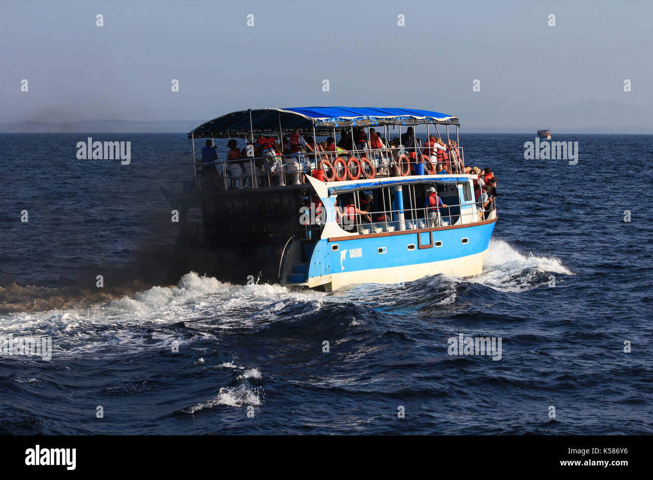 Unawatuna, Sri Lanka - January 9, 2017: A tourist boat producing black smoke and poluting the sea, during a whale watching tour. - Stock Image