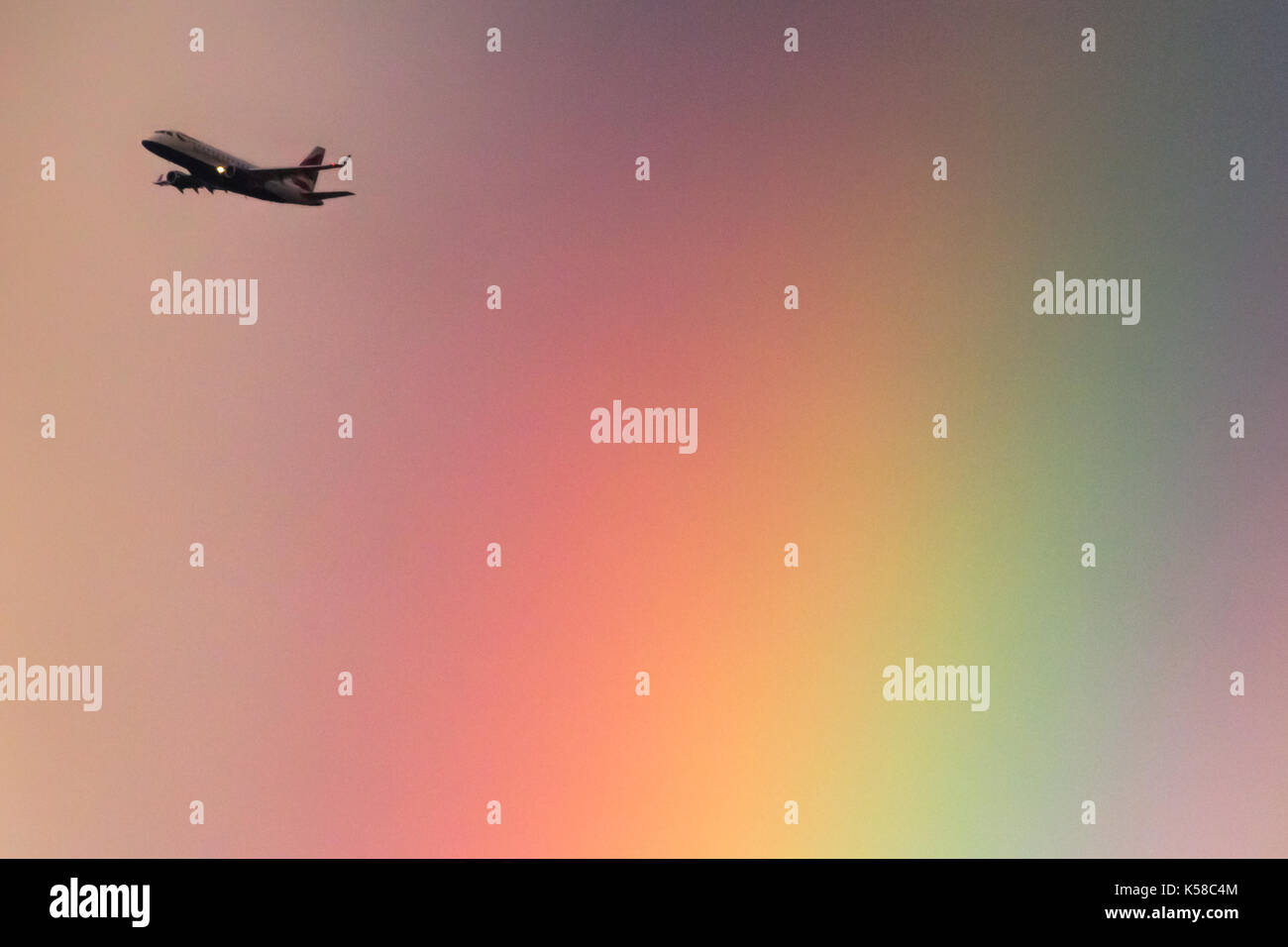 London, UK. 8th Sep, 2017. UK Weather: A British Airways passenger plane leaving City Airport passes through a sunset rainbow over the city. Credit: Guy Corbishley/Alamy Live News - Stock Image