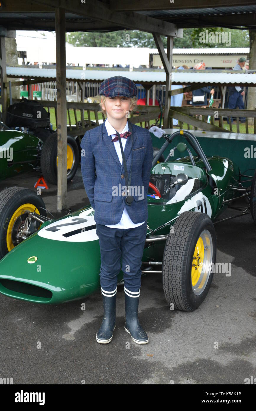 Young lad in flat cap, jacket and shirt hanging out posing in front of Lotus Climax;Goodwood Revival 8th Sept 2017 - Stock Image